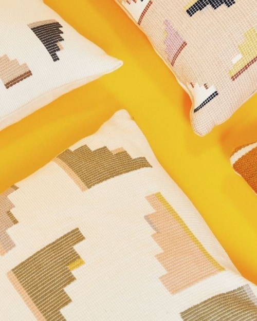 Four geometric, colorful pillows laid on the ground with a yellow background