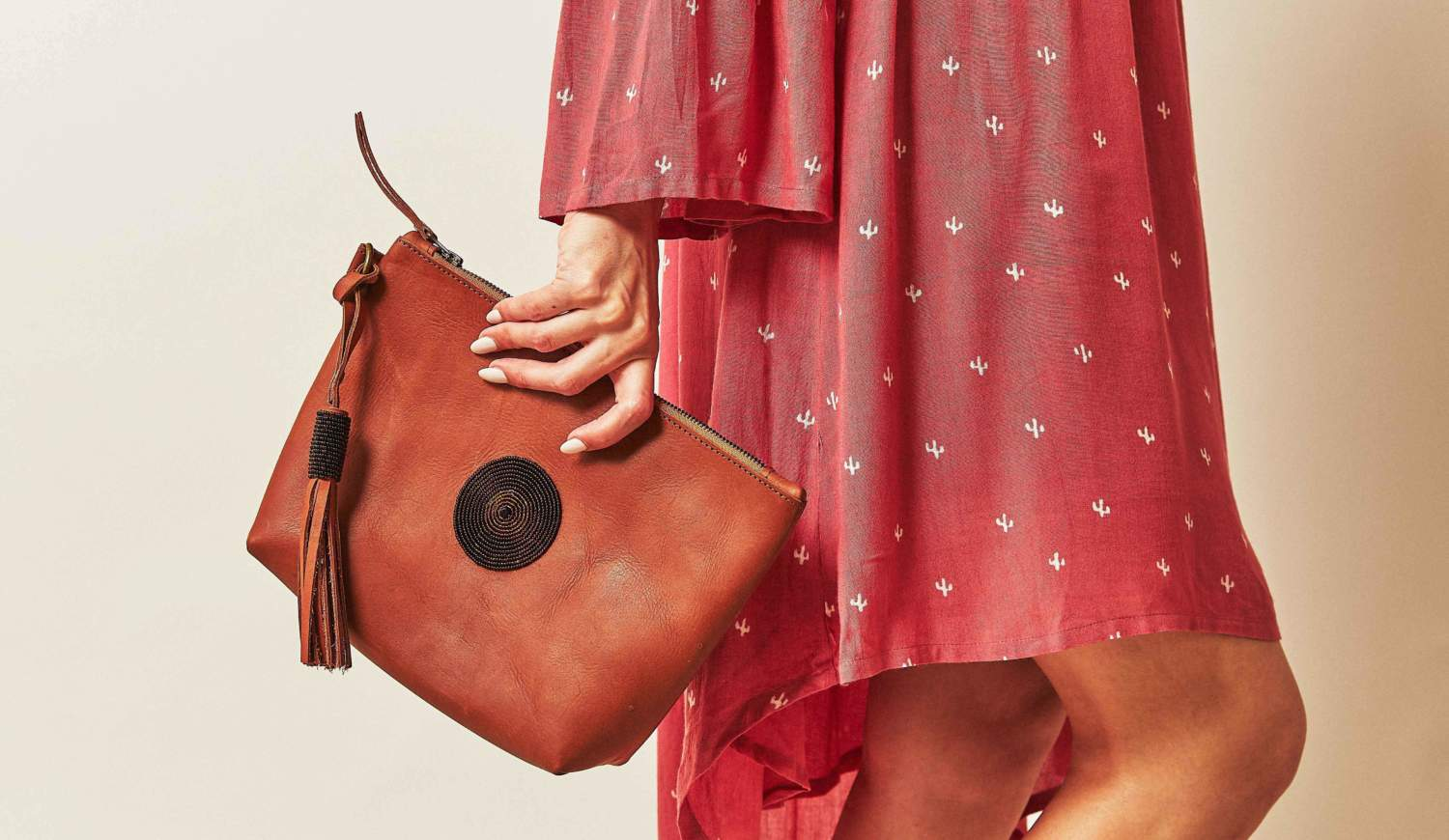 A women in a red dress with a small cactus print holds a leather clutch in her right hand