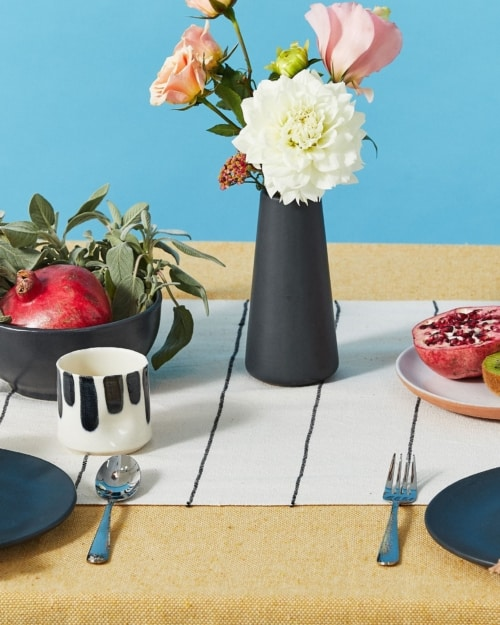 A tabletop setting with fruit and a vase and a setting for two people on a blue background