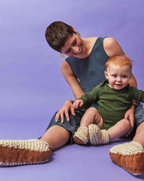 A woman and child are wearing wool slippers and sitting on a purple backdrop