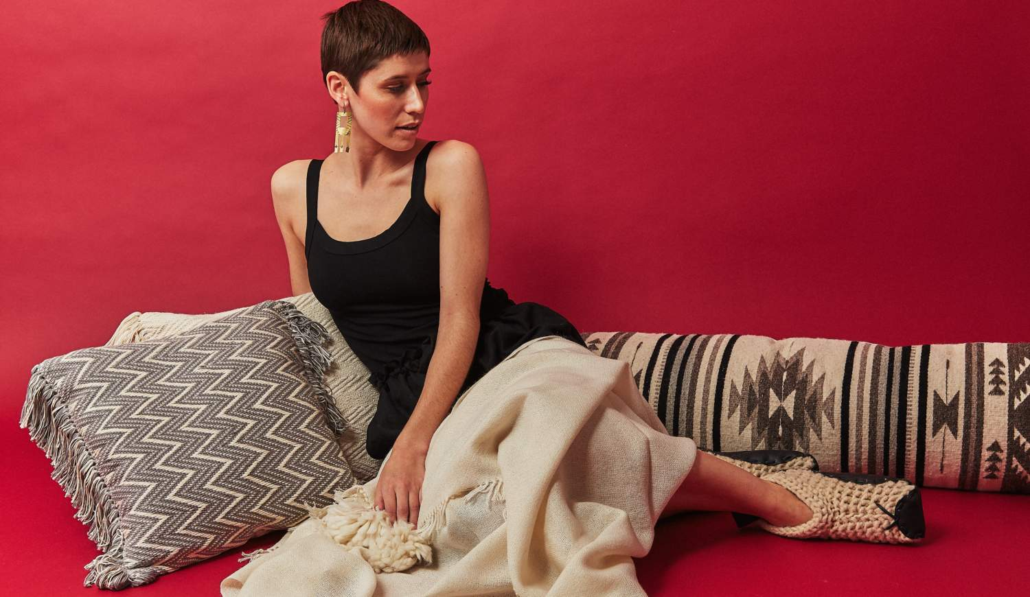 A women wearing slippers leans on a pillow and a blanket drapes over her legs