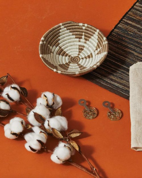 A stalk of dried cotton, napkin, placemat and bowl laying on the floor on a dark orange background