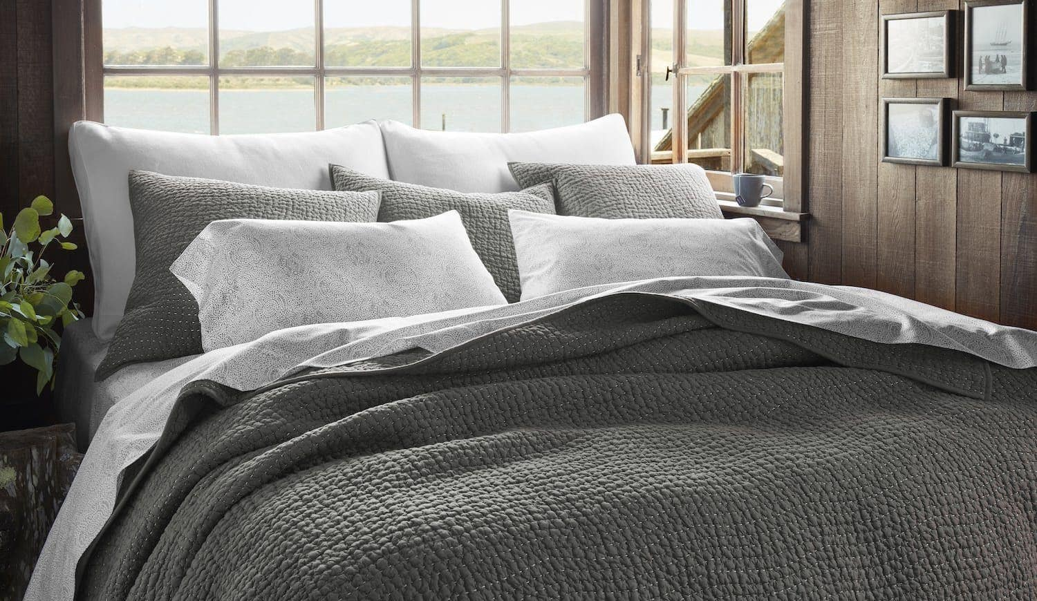 Charcoal waffle weave bedding with seven pillows with an open window overlooking water behind the bed