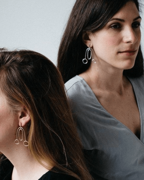 Two women with earrings sit back to back on a grey background