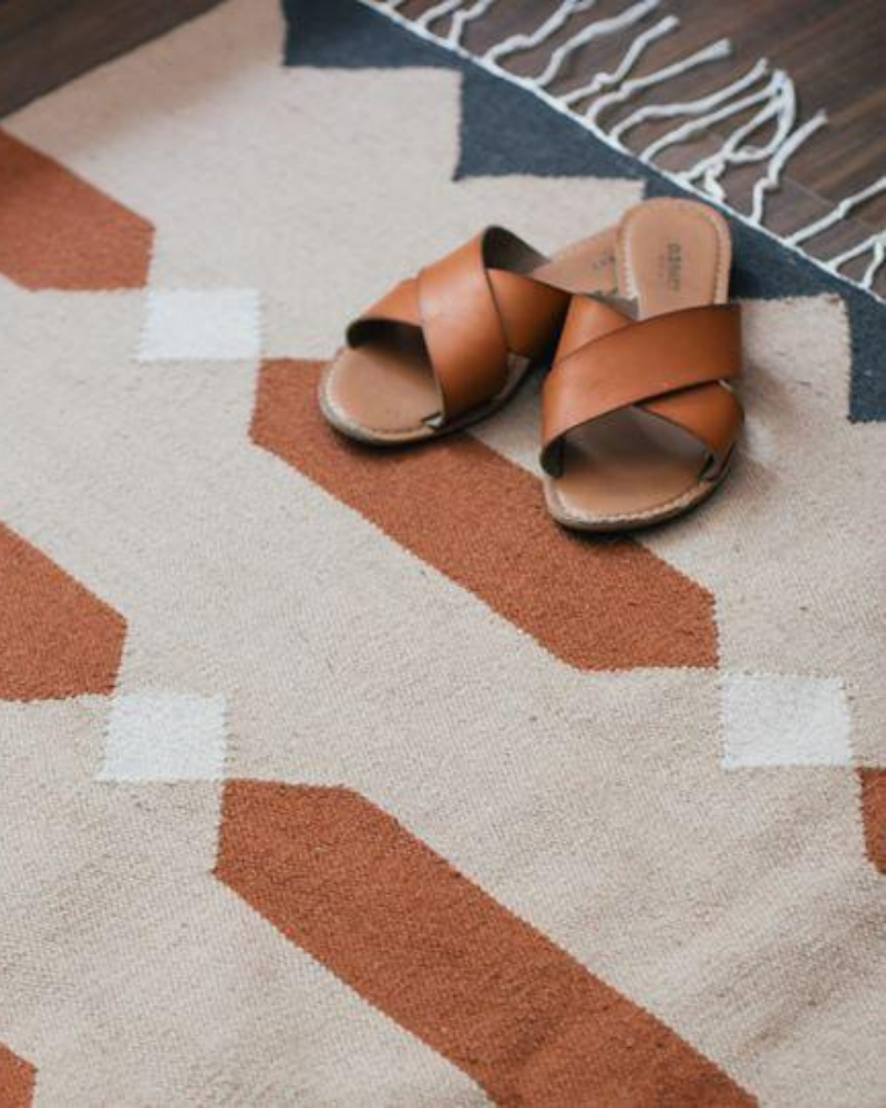 tan, orange and blue rug with white tassels