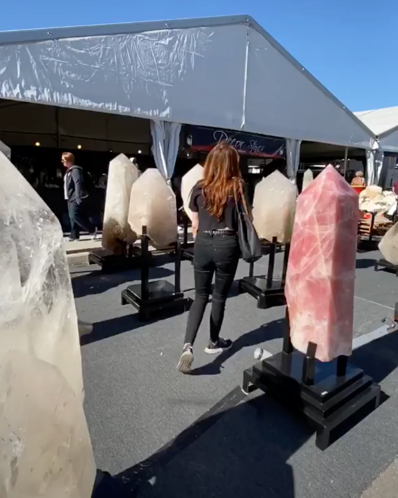 Amy Fox walking amongst several-feet-tall rose quartz and clear quartz pointed spires