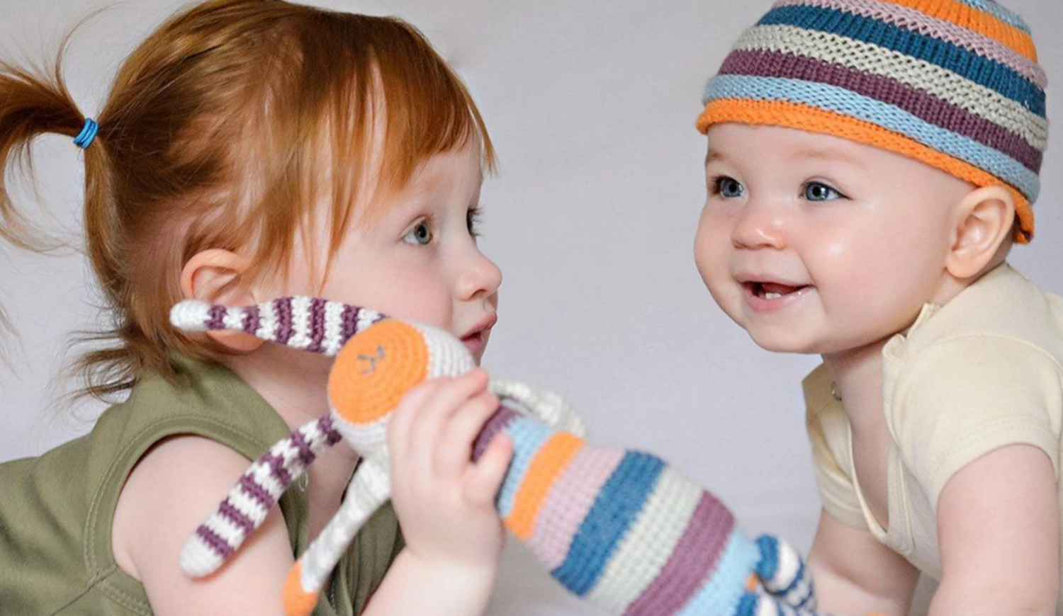 Two babies playing with a toy -Fair Trade And Eco Friendly Baby Gifts
