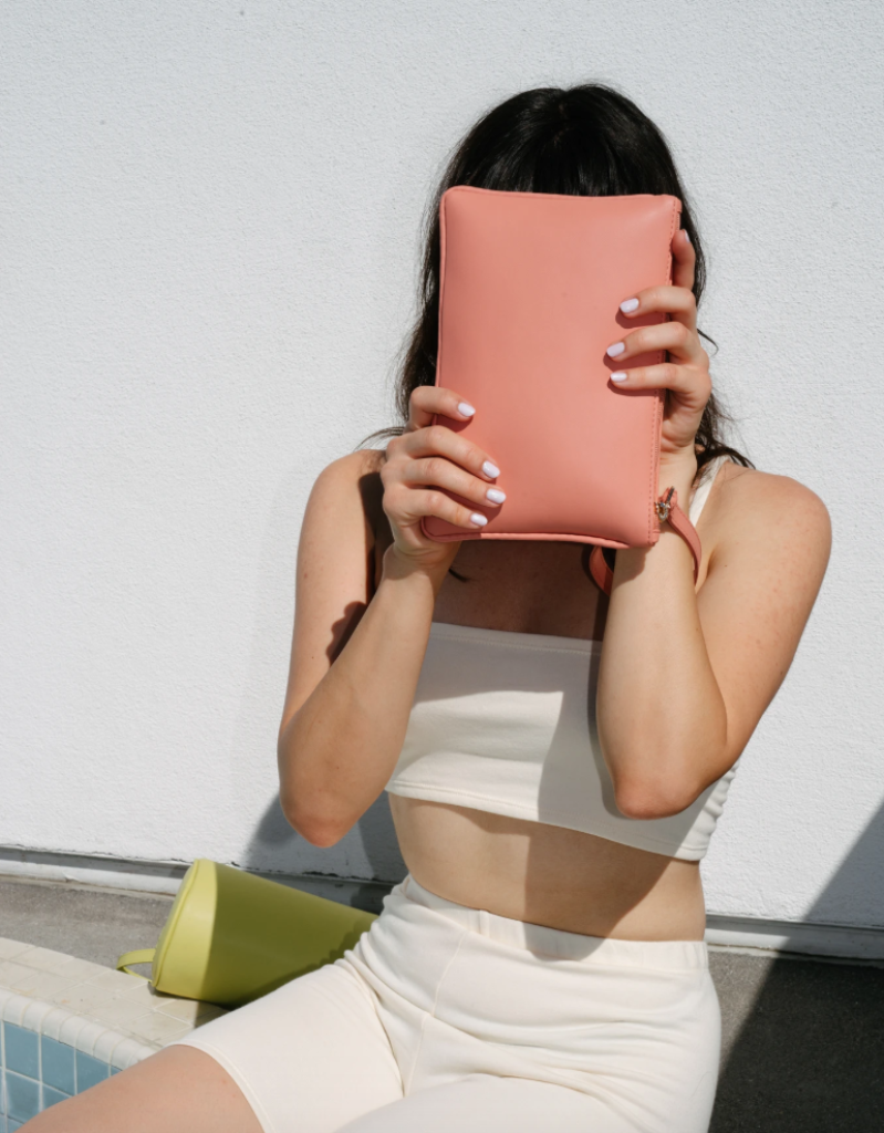 woman holding rose colored clutch