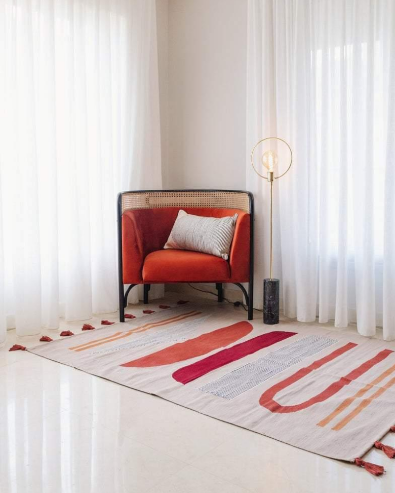 Flat woven tan rug with red and orange shapes