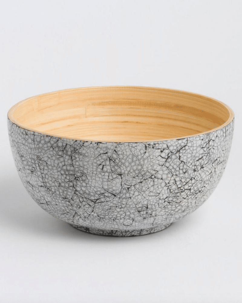 A bamboo salad bowl a natural wood texture on the inside and a white eggshell pattern on the outside