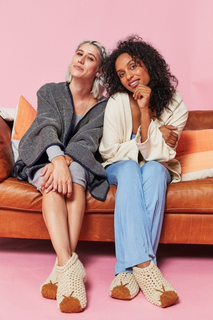 two women sitting on a couch wearing slippers