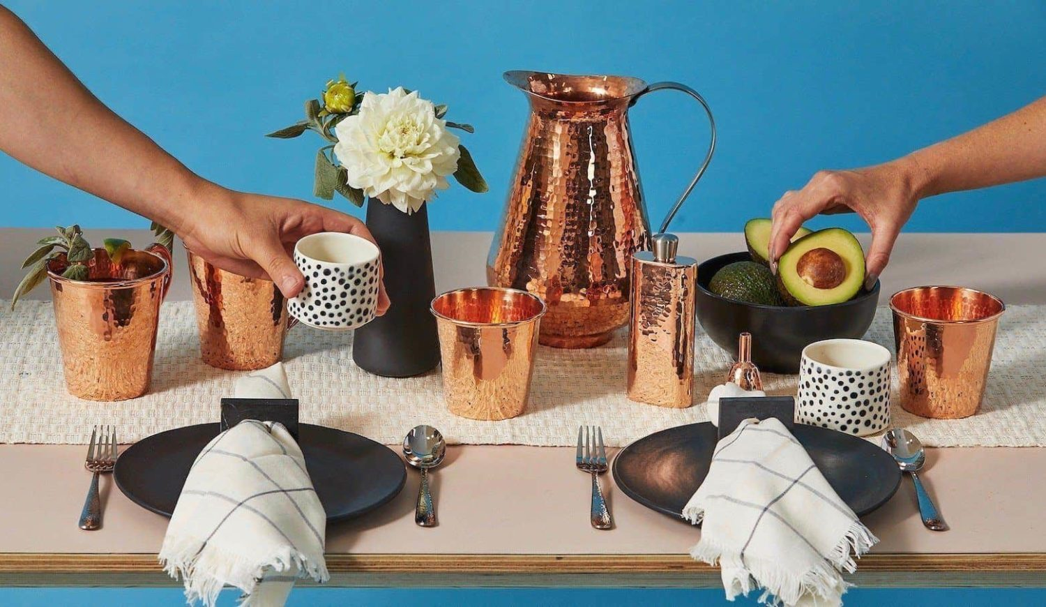 An elaborate table setting featuring large copper cups, a copper flask and a copper pitcher