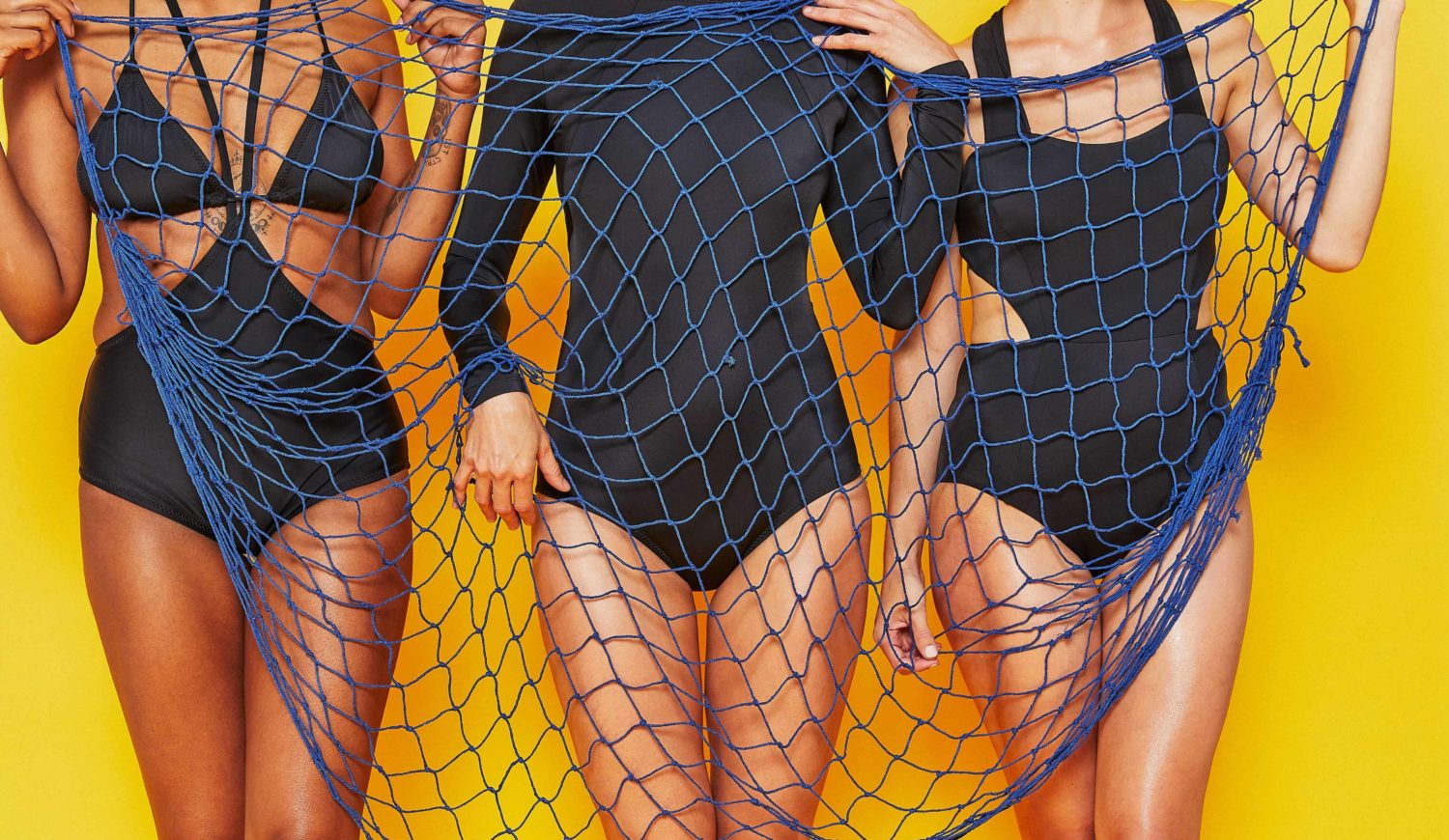 Three women standing in black swimsuits holding a blue fishing net on a yellow background