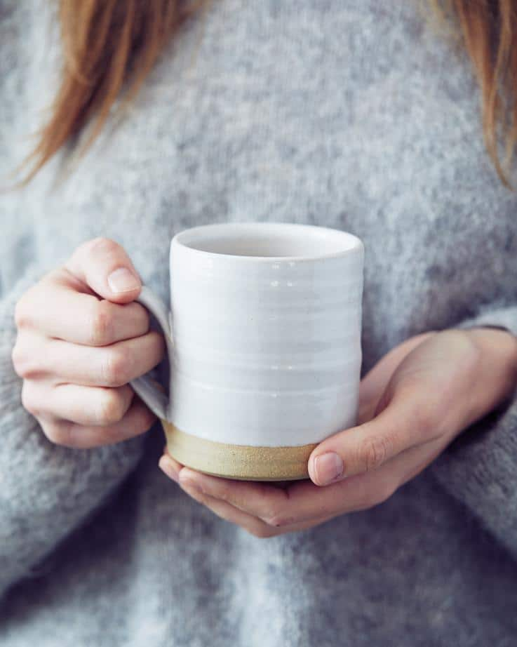 woman holding white mug