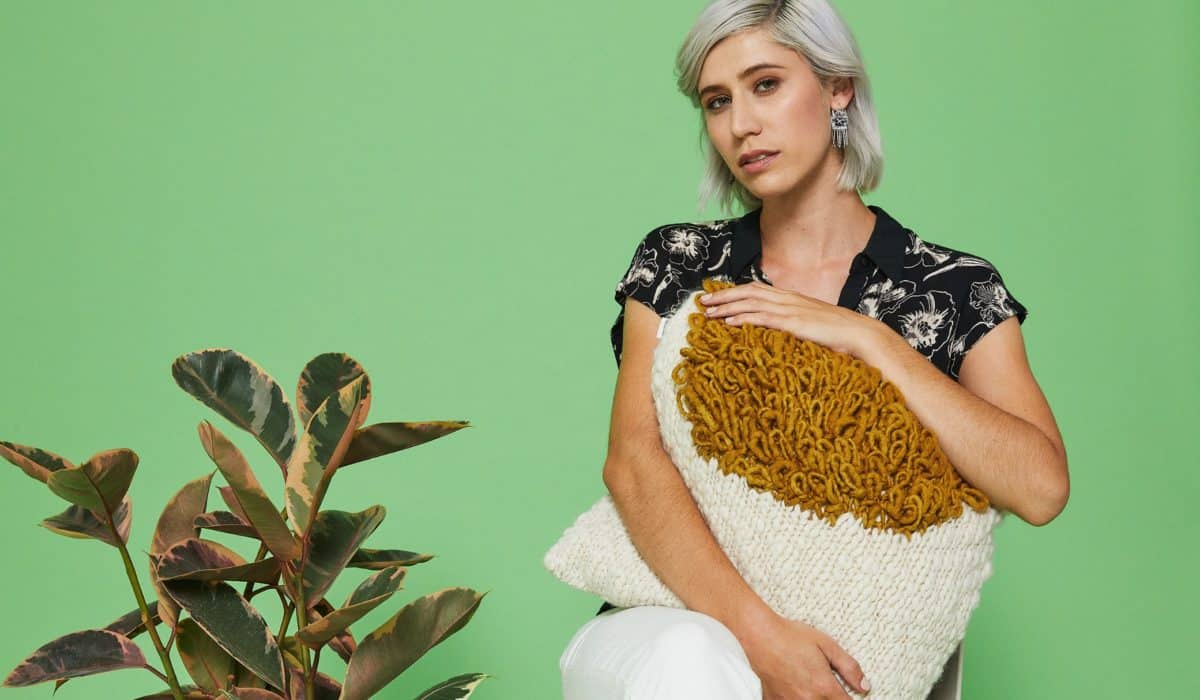 Woman holding a ethically made pillow on a green background