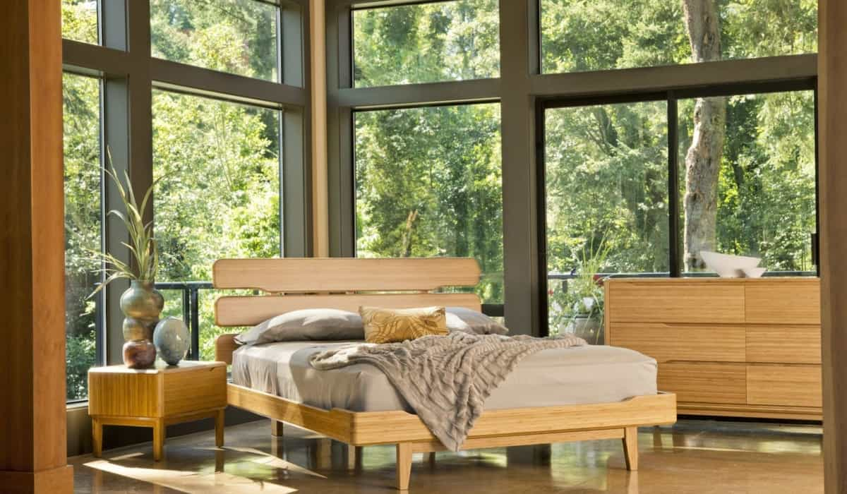 a warm pine colored bed, bedside table and dresser sit in the corner of a room in front of a floor to ceiling window