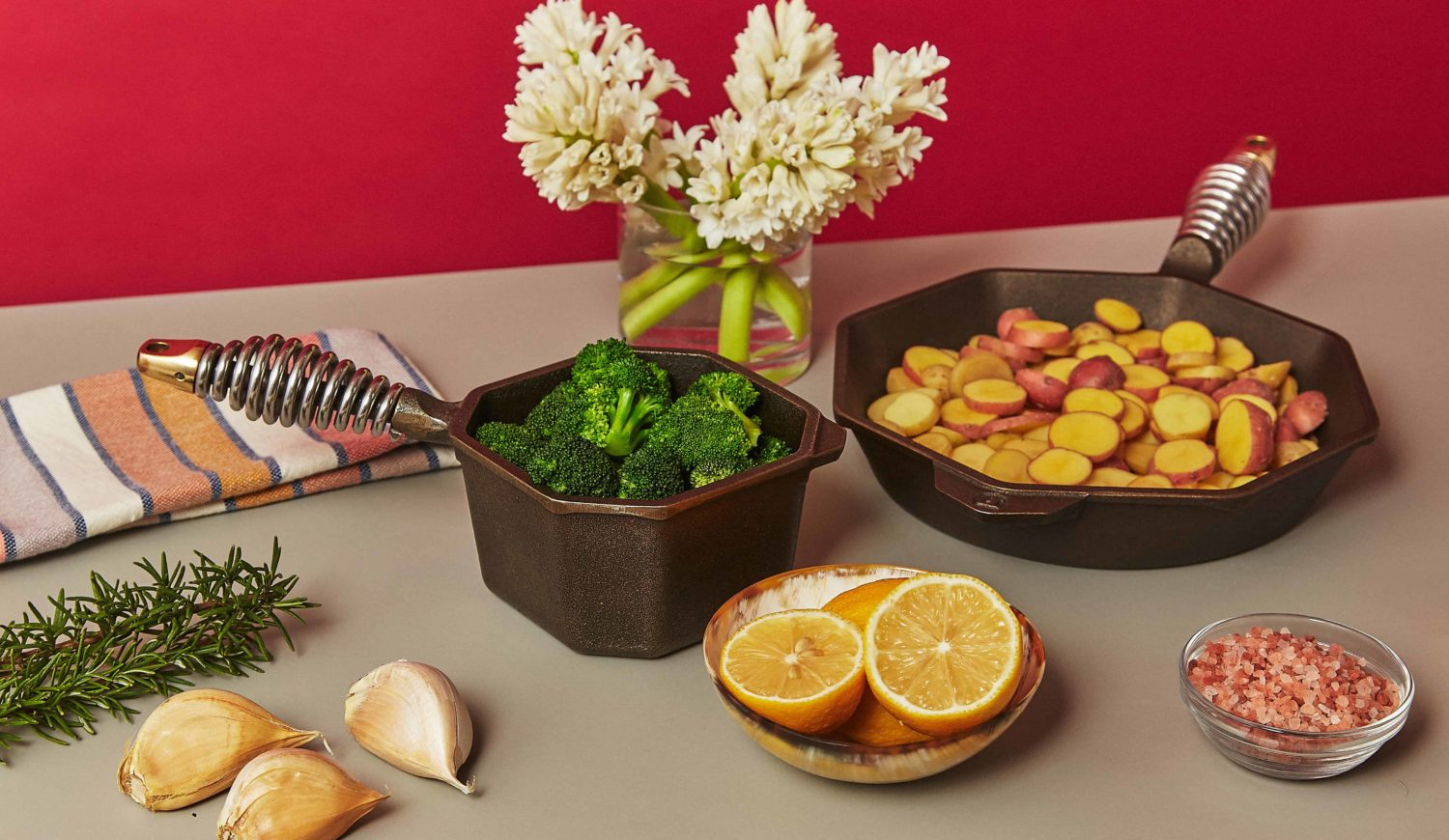 A tabletop setting with a pan full of broccoli and a pan full of cut potatoes