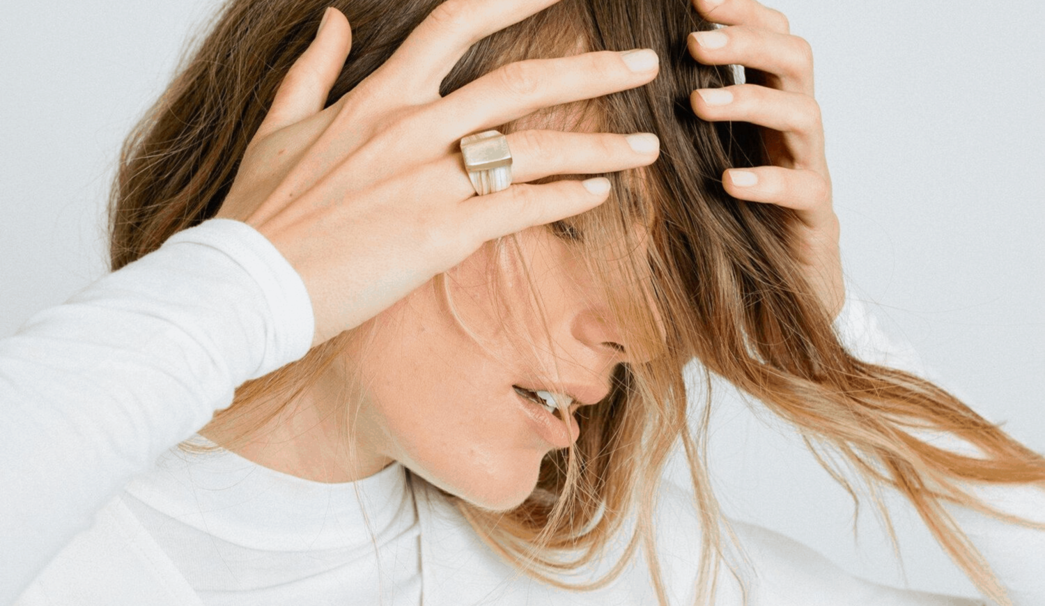 A woman wearing a large ring and a white shirt touches her head running her fingers through her hair
