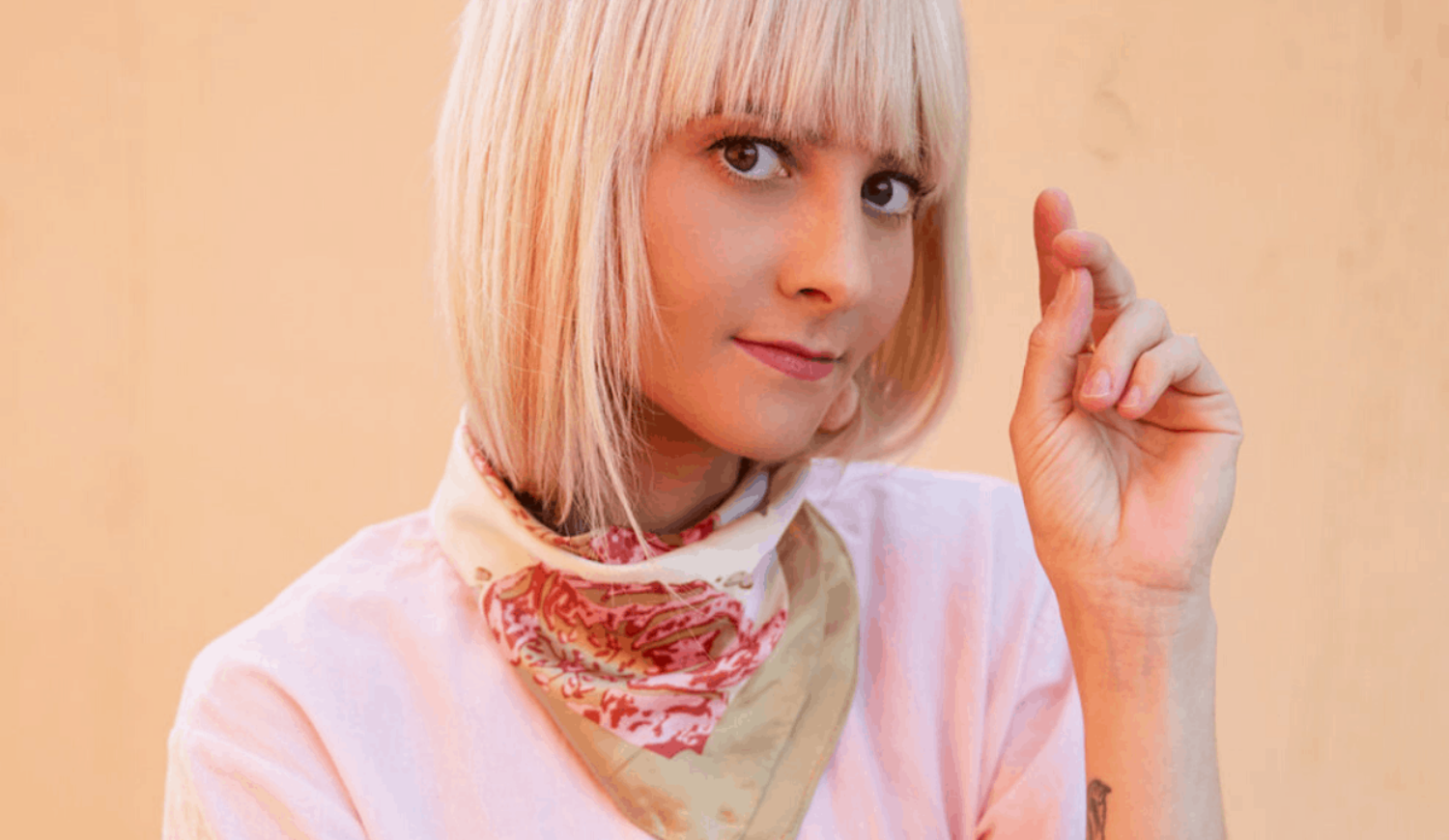 women with modern haircut in a pink tee shirt looking in camera in front of a light orange wall