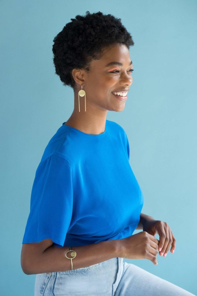 woman wearing brass statement earrings