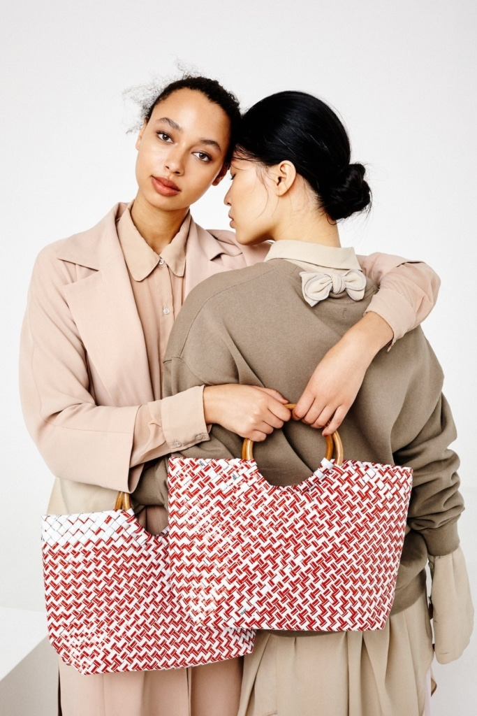 Two women holding red handbags