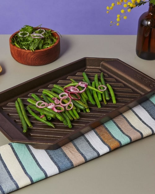 a tray of green beans and red onion are sitting on a grill pan on a gray tabletop surrounded by two bowls of salad and a brightly colored towel