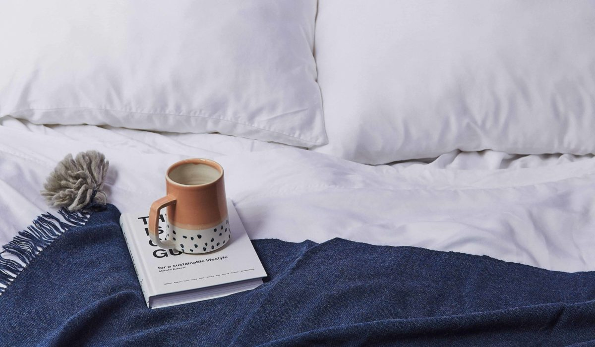 A book and a mug sit on a white bedspread with a dark blue blanket