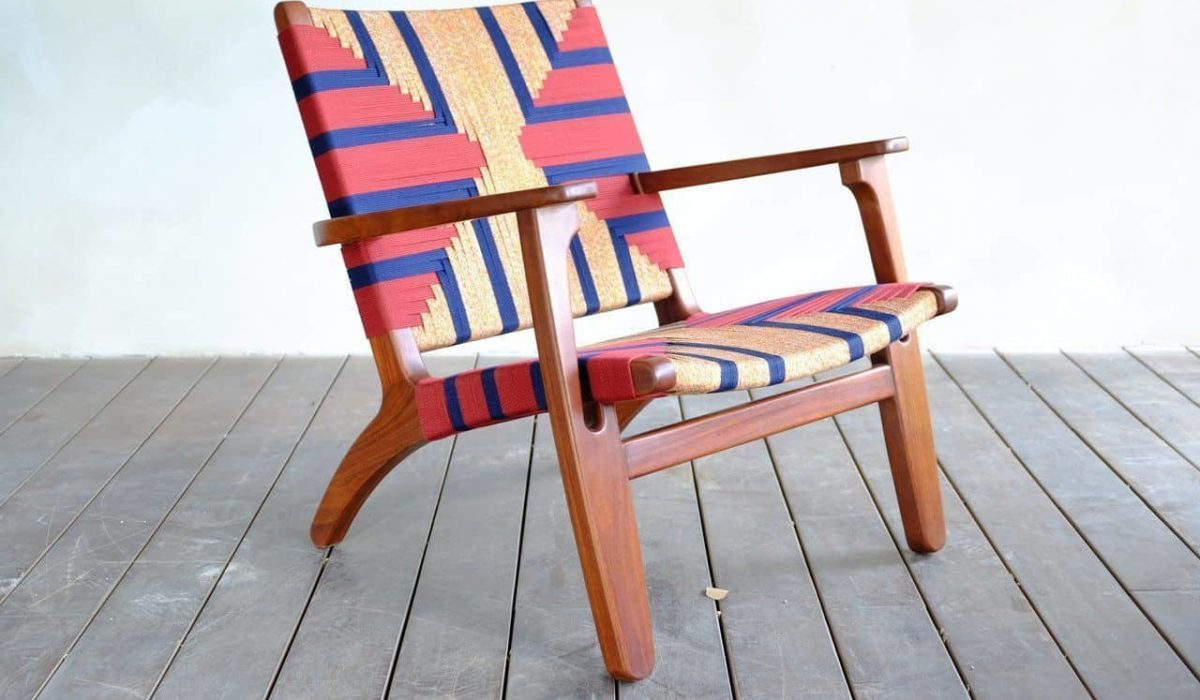 A hand woven arm chair sits on a slatted wood floor in front of a white wall
